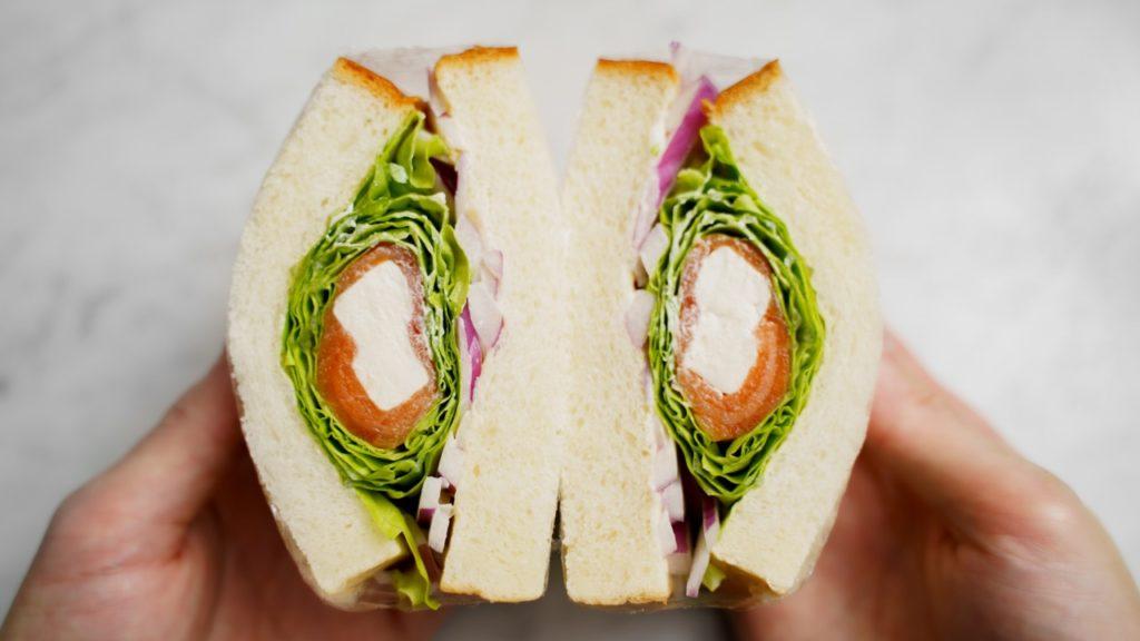 手に持ったサーモンとクリームチーズのぐるぐるサンドイッチ